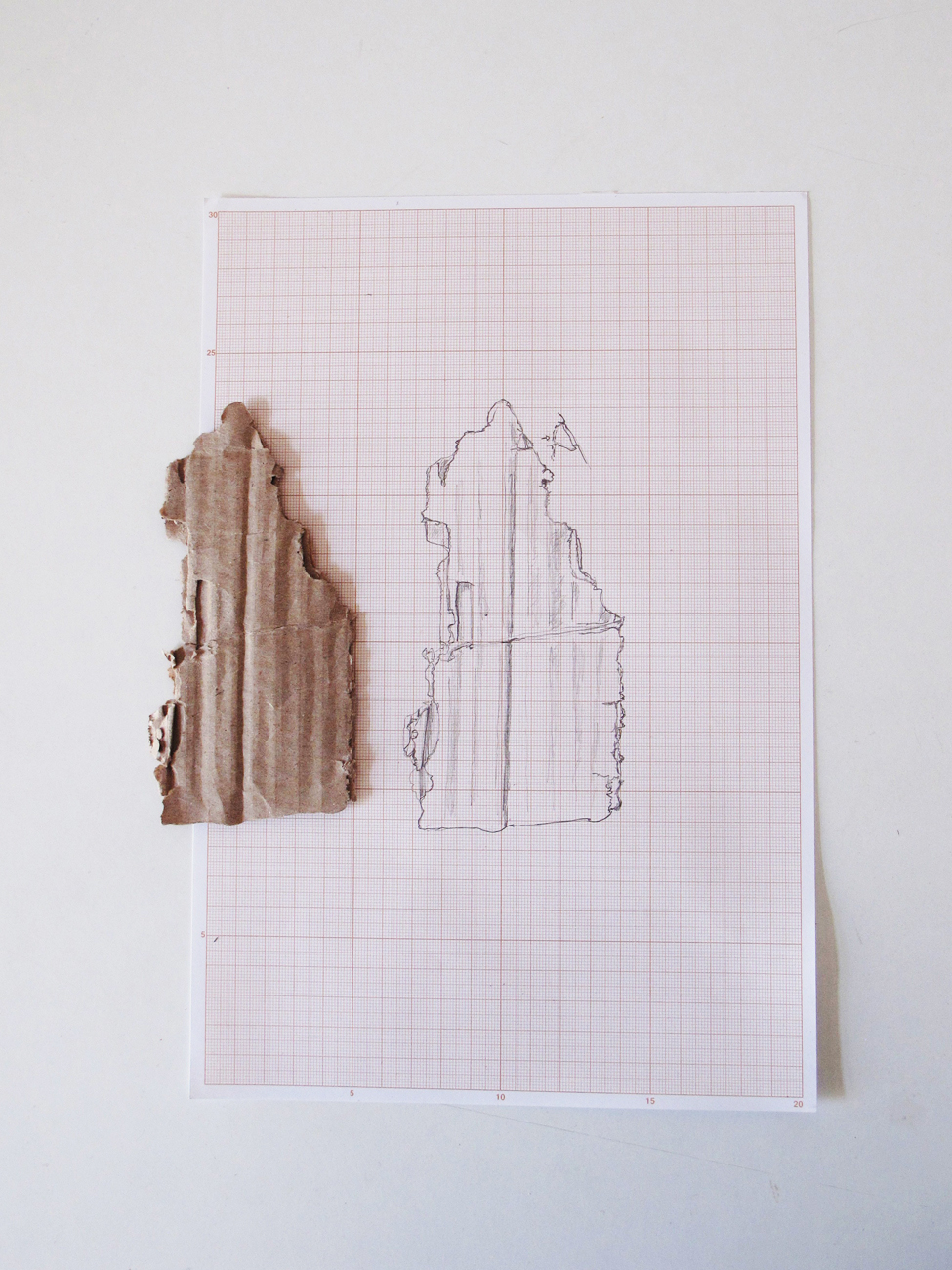 cardboard fragment next to technical drawing of it