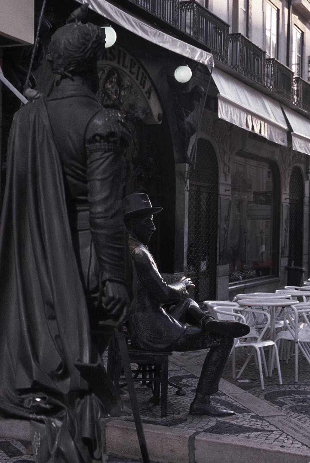 Statues of two writers gathered at a cafe.