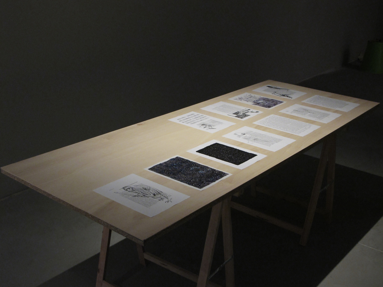 Installation view with drawings laid out on table